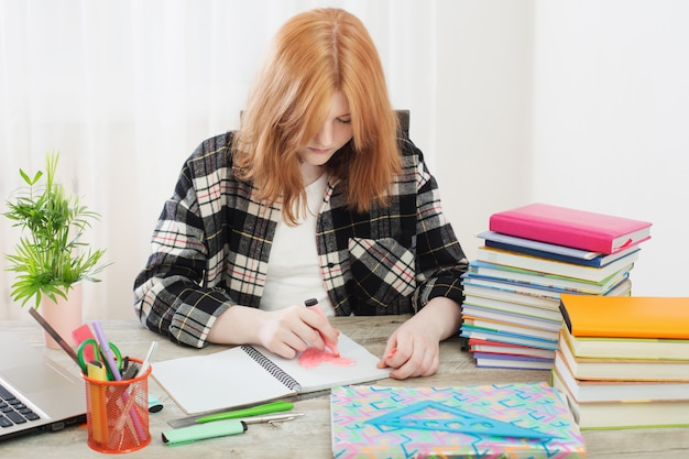 Teen girl draws  heart in  notebook, concept of first love