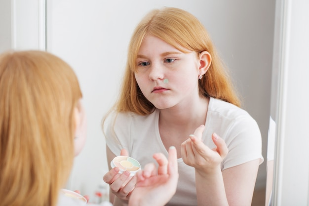 Teen girl examines acne in front of mirror