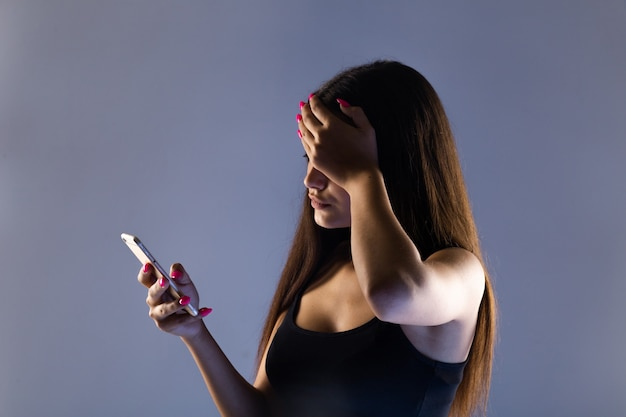 Teen girl excessively sitting at the phone at home. he is a victim of online bullying stalker social networks.