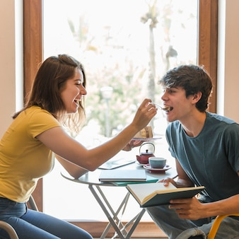 Teen girl feeding boyfriend with dessert in library