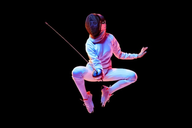 Teen girl in fencing costume with sword in hand isolated on black background, neon light.