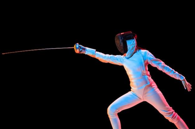 Teen girl in costume da scherma con la spada in mano isolati su sfondo nero, luce al neon.