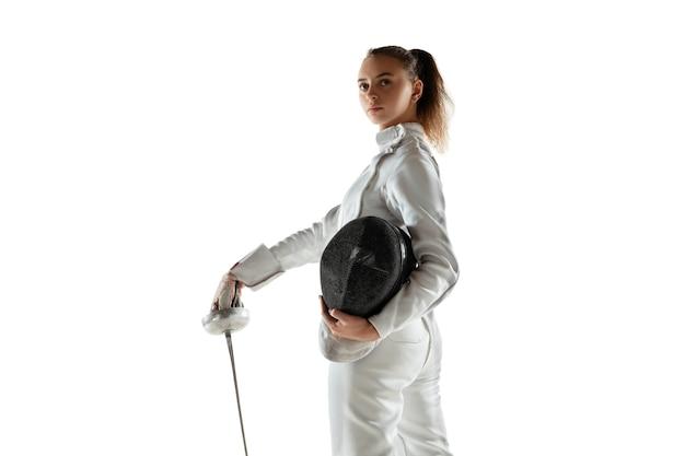 Ragazza teenager in costume da scherma con la spada in mano isolato sul muro bianco