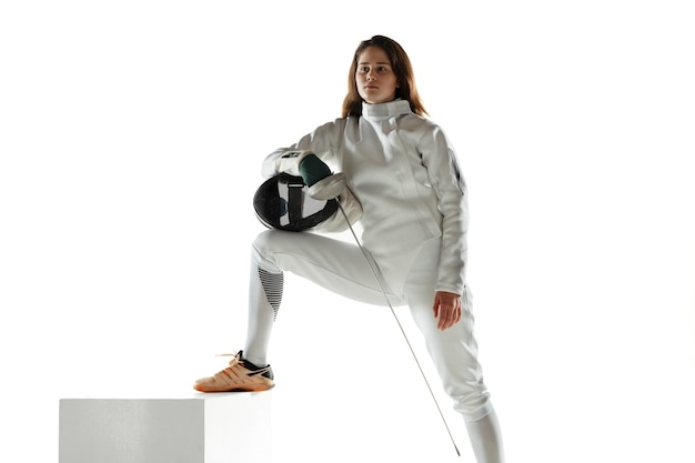 Teen girl in fencing costume with sword in hand isolated on white wall