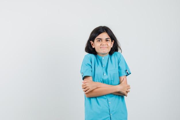 青いシャツを着て抱きしめながら寒くなる10代の少女 無料写真