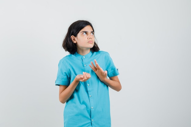 Teen girl getting into trouble in blue shirt and looking puzzled