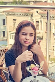Девушка-подросток счастливая улыбка, сидя в ресторане или кафе и ест мороженое. есть