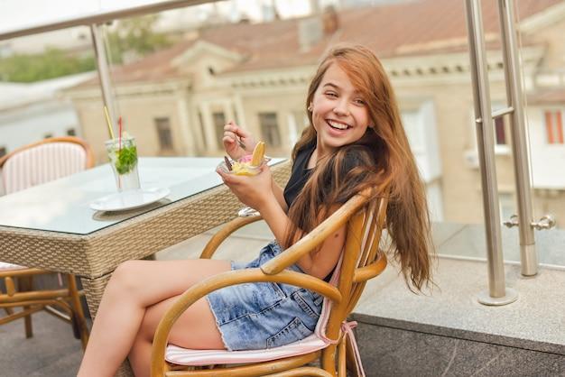 10代の少女幸せな笑顔、レストランやカフェに座って、アイスクリームを食べる
