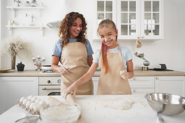 Teen girl helping her mom to cook dough in their kitchen at home