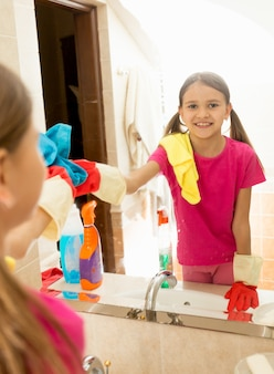 Teen girl helping at housework and cleaning bathroom mirror