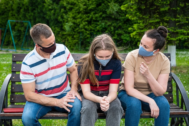 Teen girl and her parents in protective face masks quarrel outdoors