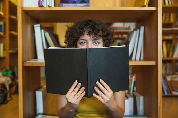 Teen girl hiding face behind book