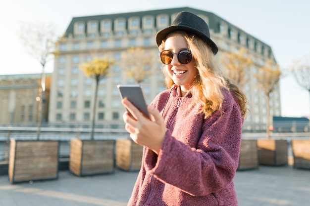Teen girl hipster in hat and glasses with mobile phone, golden hour.