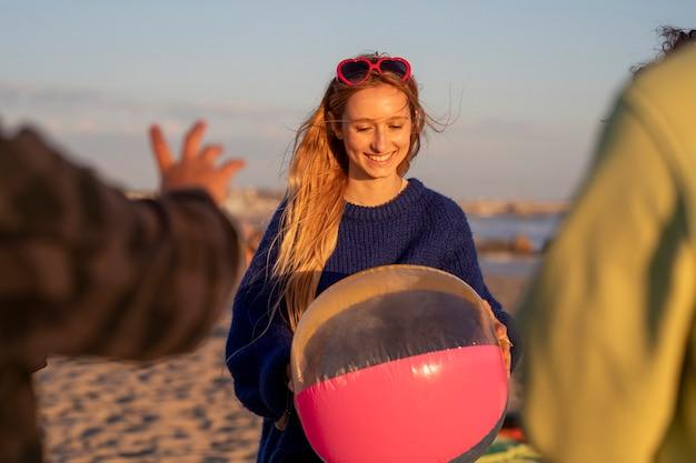 ロサンゼルスのベニスビーチで夏休みにビーチボールを保持している10代の少女