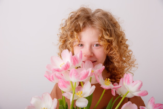 Teen girl holding a bouquet of pink tulips