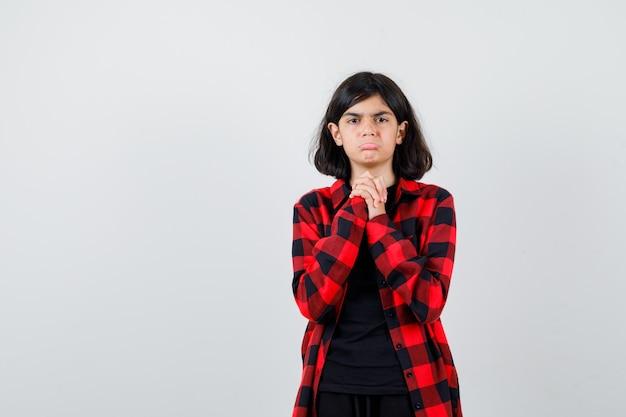 Ragazza teenager che tiene le mani giunte in gesto di supplica, curvando il labbro inferiore in camicia casual e guardando scontroso, vista frontale.