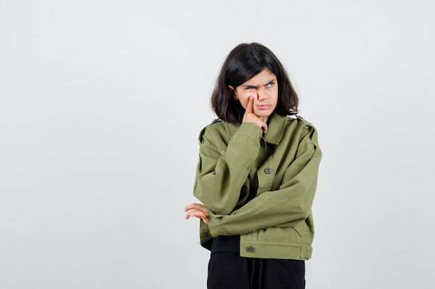 Teen girl holding finger on cheek, looking away, frowning face in army green jacket and looking upset. front view.