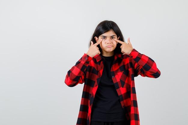 티셔츠, 체크무늬 셔츠를 입은 눈꺼풀에 손가락을 대고 무모하게 보이는 십대 소녀.