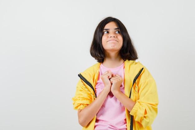 Ragazza teenager che tiene i pugni sul petto in tuta gialla, t-shirt e sembra curiosa, vista frontale.
