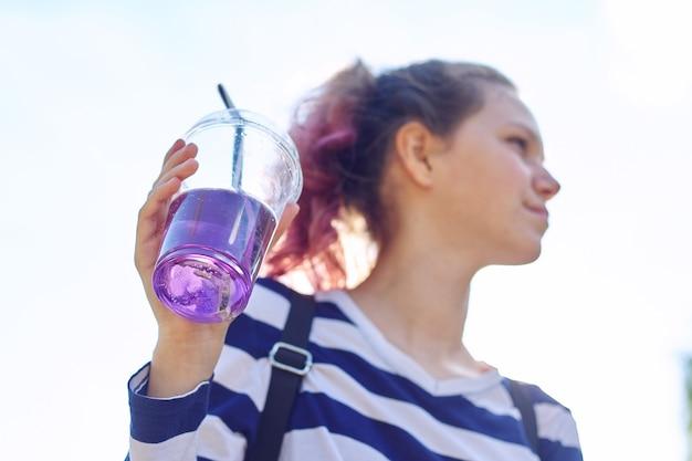 手に紫色の飲み物とストローでガラスを保持している十代の少女