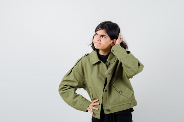 귀 뒤에 손을 잡고 군대 녹색 재킷을 멀리보고 호기심 찾고 십 대 소녀. 전면보기.