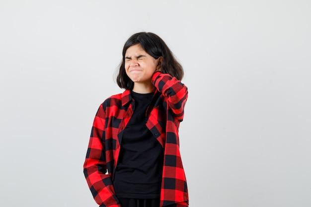 Ragazza teenager che tiene la mano dietro il collo in t-shirt, camicia a scacchi e sembra dolorosa, vista frontale.