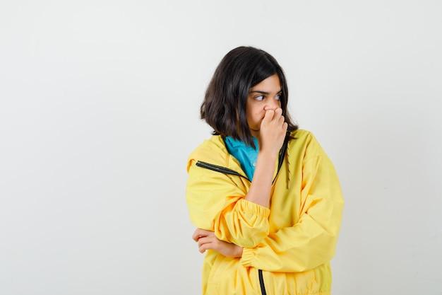 あごに手をつないで、黄色いジャケットで目をそらし、心配そうに見える十代の少女、正面図。