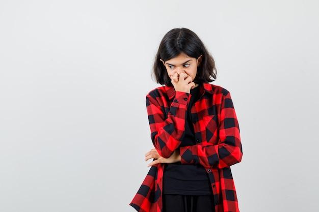 10대 소녀가 티셔츠, 체크무늬 셔츠를 입고 손을 잡고 사려깊은 표정을 짓고 있습니다. 전면보기.