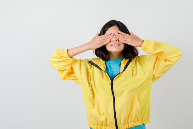 Teen girl holding hands on eyes in yellow jacket and looking merry , front view.
