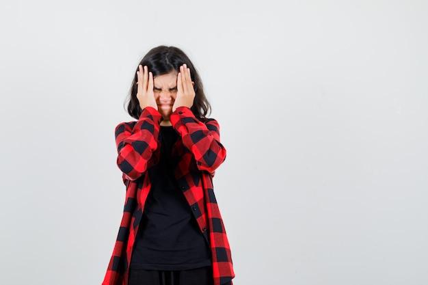 Ragazza teenager che si tiene per mano sul viso in t-shirt, camicia a scacchi e sembra infastidita. vista frontale.