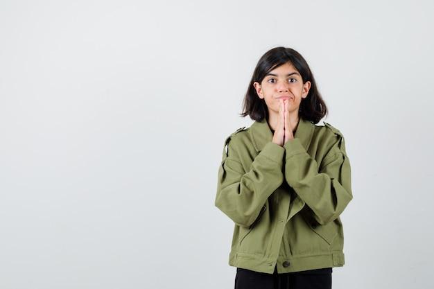軍の緑のジャケットで祈りのジェスチャーで手をつないで、焦点を当てて、正面図を探している十代の少女。