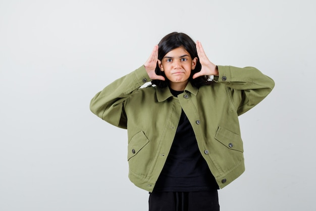 Teen girl holding hands near face in green jacket and looking dissatisfied , front view.