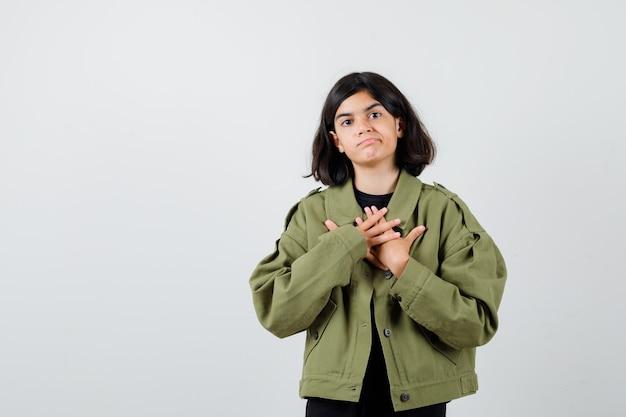 10대 소녀가 티셔츠, 재킷을 입고 가슴에 손을 대고 무모하게 보입니다. 전면보기.