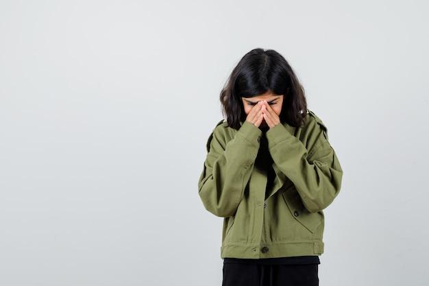 군대 녹색 재킷에 얼굴에 손을 잡고 슬픈 찾고 십 대 소녀, 전면 보기.