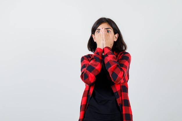 10대 소녀는 티셔츠, 체크무늬 셔츠를 입고 얼굴에 손을 대고 겁에 질려 앞을 바라보고 있습니다.