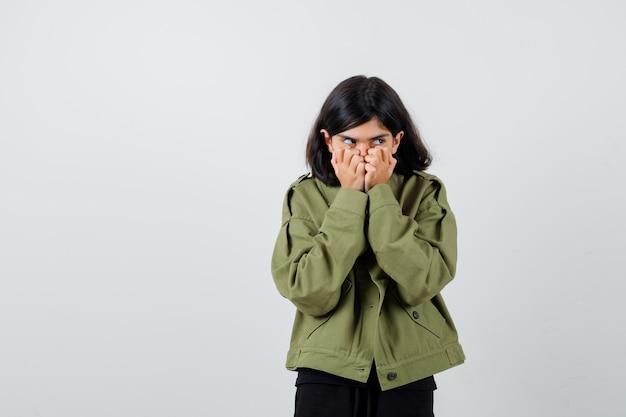 Tシャツ、ジャケットで口に手をつないで臆病に見える10代の少女。正面図。