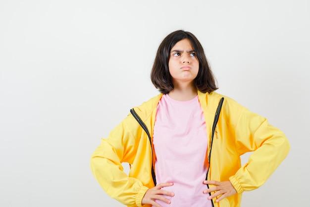 Tシャツ、ジャケットで腰に手をつないで怒っているように見える10代の少女。正面図。