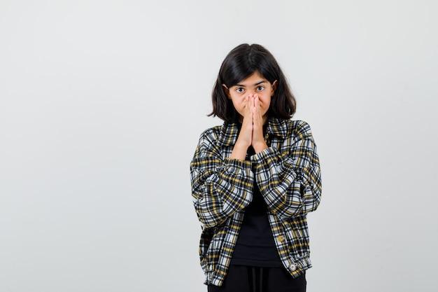 Ragazza teenager che si tiene per mano nel gesto di preghiera in camicia casuale e sembra messa a fuoco, vista frontale.