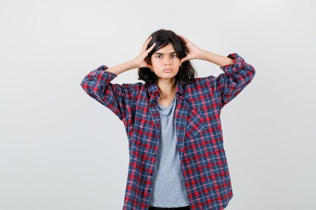 Девушка-подросток держит голову пальцами в клетчатой рубашке и выглядит усталой, вид спереди.