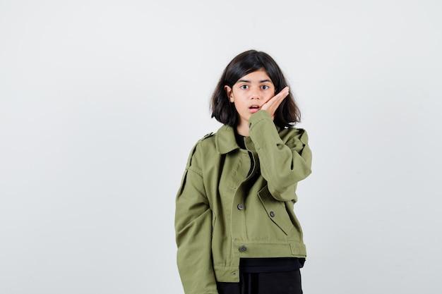 Ragazza teenager che tiene la palma vicino alla bocca in giacca verde e sembra sorpresa, vista frontale.