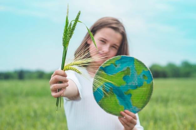 Девушка-подросток держит в руках планету и зеленые колоски пшеницы