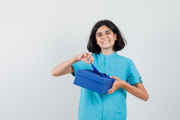 Ragazza teenager che tiene casella attuale mentre sorride in camicia blu e sembra felice.