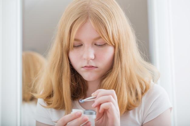 Teen girl holds blue eye lens