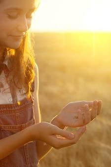 10대 소녀는 일몰 시간에 밀알을 손에 쥐고 있다