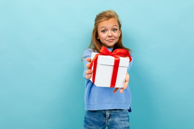 Teen girl holds out a gift with a red ribbon on a light blue