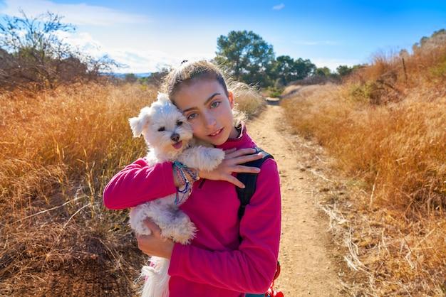 Teen girl hug maltichon in outdoor