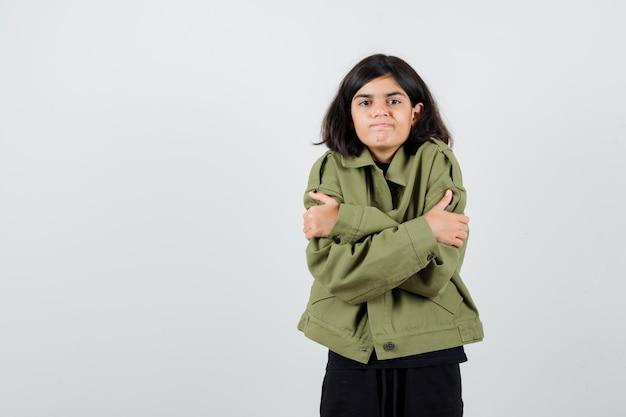 軍の緑のジャケットに身を抱き、失望しているように見える十代の少女、正面図。