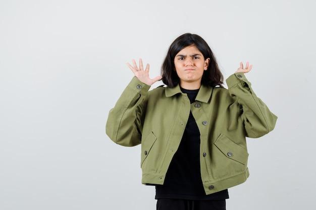 Девушка в зеленой куртке армии показывает жест капитуляции и выглядит унылой, вид спереди.