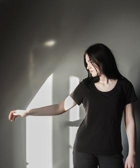 검은 청바지에 십 대 소녀와 햇빛에 배경 회색 벽에 티셔츠
