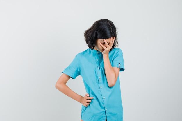 그녀의 얼굴에 손을 잡고 우울 찾고 파란색 셔츠에 십 대 소녀